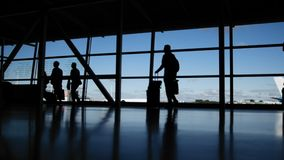 Travellers with suitcases and baggage in airport walking to departures in front of window, silhouette. Blue colors stock footage