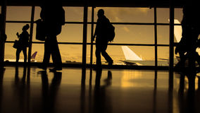 Travellers with suitcases and baggage in airport walking to departures in front of window, silhouette, warm Stock Images