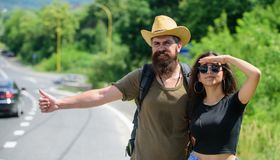 Travellers try to stop car. Couple hitchhikers travelling summer sunny day. Couple travelers man and girl hitchhiking at Stock Photo
