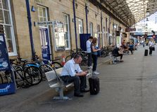 Travellers use mobile phones at Huddersfield Station. Huddersfield, West Yorkshire, United Kingdom - June 25 2018: Travellers use mobile phones at Huddersfield royalty free stock photos