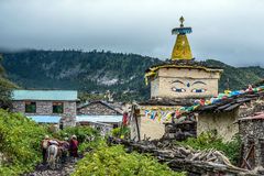 Travellers walk by the Buddhist temple in Nepal Royalty Free Stock Photography