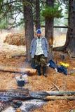 Travellier accanto ai fuochi di accampamento in legno Immagini Stock Libere da Diritti