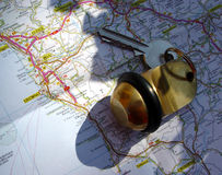 Travelling. Hotel room key on a map in natural sunlight Stock Photography