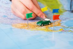 Travelling abroad by car background. Travelling abroad by car concept. Female hand tackling country with flag-pin on the map. Tourism and vacation background Stock Photography