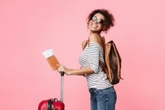Travelling abroad. Happy tourist woman with passport. And suitcase over pink background stock images