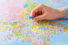 Travelling background. Hand tackling county on the map. Travelling background. Female hand tackling country with flag-pin on the map. Tourism and vacation Royalty Free Stock Photo
