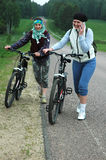 Travelling with bikes. Two young smiling women travelling with bikes, one of them is speaking on mobile phone Stock Images