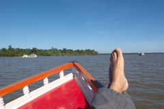 Travelling by boat in Amazon. A relaxing trip scene. In the foreground, a red sharp boat bow, the feet's traveler. The river is wide, with haze water. In the Royalty Free Stock Photos
