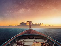 Travelling by boat at night on the ocean, in dawn with starry sky and sunlight over horizon stock photo