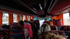 View inside the bus cabin with tourists traveling on an exotic road with palm trees. Travelling bus with tourists. View inside the bus cabin with tourists stock video