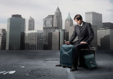 Travelling for business. Portrait of a businessman sitting on his luggage in the middle of a citystreet Royalty Free Stock Photography