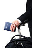 Travelling businessman. An isolated a travelling businessman carrying a passport and a luggage Stock Image