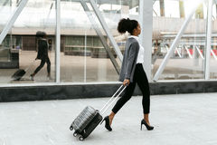 Travelling businesswoman walking with luggage at station Royalty Free Stock Images