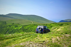 Travelling by car in a mountain pasture Stock Photography
