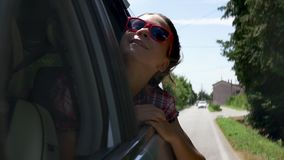 Travelling by car. Woman leaning out of window. Happy smiling woman leans out of the car window during road trip in Europe stock video