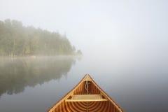 Travelling by Cedar Canoe. Bow of a Cedar Canoe and Misty Shoreline - Haliburton, Ontario, Canada stock images