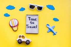 Travelling with child concept. Air balloon, car and plane. Time to travel hand lettering in notebook on yellow. Background top view copy space stock images