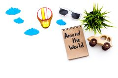 Travelling with child concept. Airplan and car toy, air balloon cookie. Around the world hand lettering in notebook on. White background top view Royalty Free Stock Image