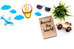 Travelling with child concept. Airplan and car toy, air balloon cookie. Around the world hand lettering in notebook on. White background top view Royalty Free Stock Photography