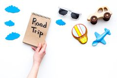 Travelling with child concept. Airplan and car toy, air balloon cookie. Road trip hand lettering in notebook on white. Background top view Stock Image