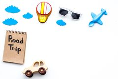 Travelling with child concept. Airplan and car toy, air balloon cookie. Road trip hand lettering in notebook on white. Background top view Stock Photos