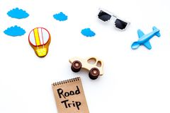 Travelling with child concept. Airplan and car toy, air balloon cookie. Road trip hand lettering in notebook on white. Background top view Royalty Free Stock Photography