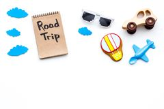 Travelling with child concept. Airplan and car toy, air balloon cookie. Road trip hand lettering in notebook on white. Background top view Royalty Free Stock Image