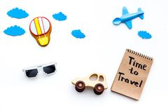 Travelling with child concept. Airplan and car toy, air balloon cookie. Time to travel hand lettering in notebook on. White background top view Royalty Free Stock Photo