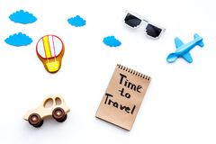 Travelling with child concept. Airplan and car toy, air balloon cookie. Time to travel hand lettering in notebook on. White background top view Royalty Free Stock Images