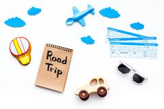 Travelling with child concept. Airplan toy, air balloon cookie, airplan tickets. Road trip hand lettering in notebook on. White background top view Royalty Free Stock Image