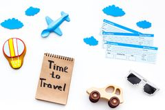 Travelling with child concept. Airplan toy, air balloon cookie, airplan tickets. Time to travel hand lettering in. Notebook on white background top view Stock Photos
