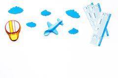 Travelling with child concept. Airplan toy, air balloon cookie, airplan tickets on white background top view copy space. Travelling with child concept. Airplan Stock Image
