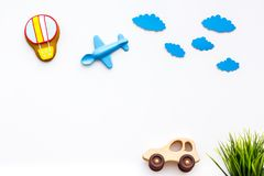 Travelling with child concept. Car and airplan toy, air balloon cookie on white background top view copy space. Travelling with child concept. Car and airplan Royalty Free Stock Photography