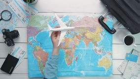 Travelling concept Top view traveler`s hand flying a toy airplane above the world map at white wooden desk. Travelling concept. Top view traveler`s hand flying a stock footage