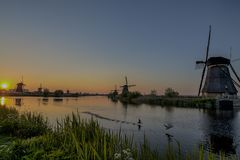 Travelling Concepts and Ideas. UNESCO Heritage Dutch Windmills. In Front of The Canal and Sun at Kinderdijk Located in Traditional Village in Holland, The Royalty Free Stock Photos