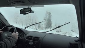 Travelling on a country road in bad weather. Man drives in his car in harsh snowy conditions, with slush, wind and snowfall stock video footage