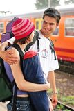 Travelling couple. Girl and a boy travelling with  backpacks-at a train station Royalty Free Stock Photos