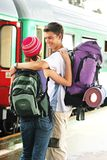 Travelling couple. Girl and a boy travelling with  backpacks-at a train station Stock Image