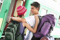 Travelling couple. Girl and a boy travelling with  backpacks-at a train station Stock Images