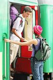 Travelling couple. Girl and a boy travelling with  backpacks-at a train station Royalty Free Stock Photography