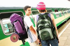 Travelling couple. Girl and a boy travelling with  backpacks-at a train station Stock Photography