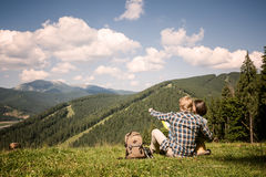 Travelling couple sitting on the alpine meadow Stock Image