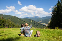 Travelling couple sitting on the alpine meadow Royalty Free Stock Photography