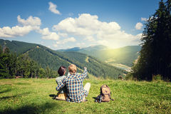 Travelling couple sitting on the alpine meadow. And looking at the map Royalty Free Stock Photo