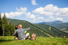 Travelling couple sitting on the alpine meadow. And looking at the map Royalty Free Stock Images