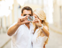 Travelling couple taking photo picture with camera Royalty Free Stock Images