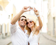 Travelling couple taking photo picture with camera Royalty Free Stock Image