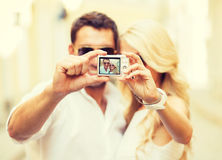Travelling couple taking photo picture with camera Royalty Free Stock Photos