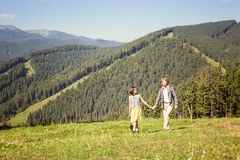 Travelling couple walking together. At the summer meadow and looking around mountain view royalty free stock photos