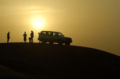Travelling in the desert. Group of young people standing near the car in the desert. Sunset sky background royalty free stock photo